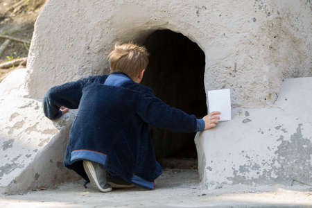 Boy child looks into the cave.Curious baby looks into the unknown Banque d'images