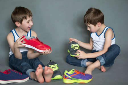 Two twin brothers choose shoes. Boys are sitting on the floor with sneakers.