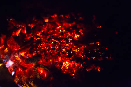 Burning embers of a fire on a black background.
