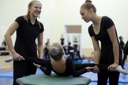 Indicative training circus school. Gymnastic workout for children. The coach stretches the child to the gymnastic twine. Stretching gymnast muscles
