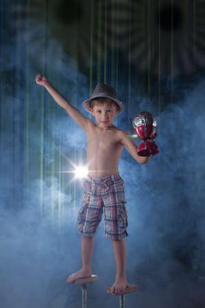 Little boy circus artist on stage. Circus kids. Performs child acrobat. Training a little juggler