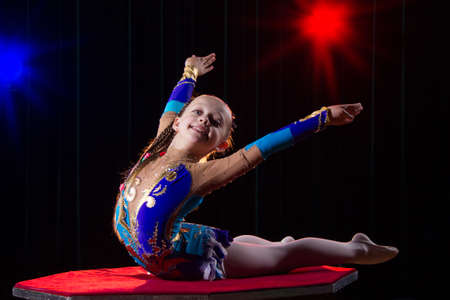 A girl with a flexible body. Performs a circus artist. Circus gymnast. Balancing act. The child performs an acrobatic trick Banque d'images