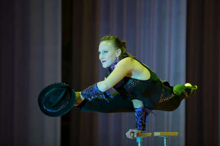 Indicative training circus school.Acrobatic performance of the actress.Girl with a flexible body.Balancing act.Twine figure on stage