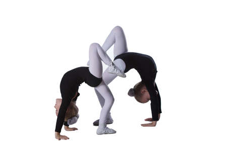 Girls gymnasts on a white background. Two little acrobats perform a number