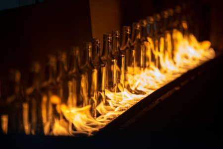 Glassworks. Glass industry. Glass bottle on conveyor on fire