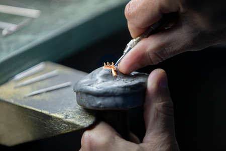 Hands make a golden decoration. Jewelry industry, Precious ring making. Archivio Fotografico
