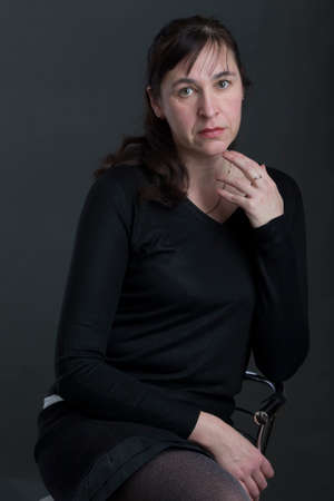 Studio portrait of an ordinary middle-aged woman.Forty year old woman on gray background