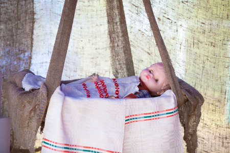 Ethnic Slavic doll in a cradle with an embroidered shirt.