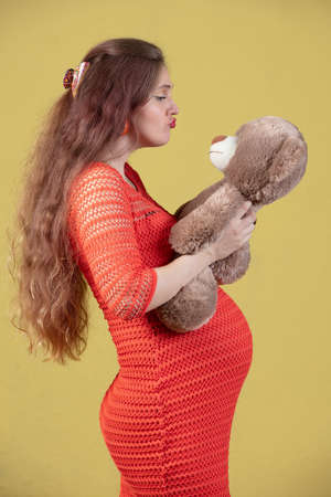 Beautiful pregnant woman with a teddy bear.