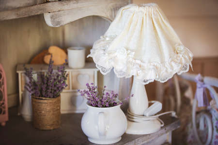 Still life in the style of provence. White lampshade dry lavender flowers stand on a table