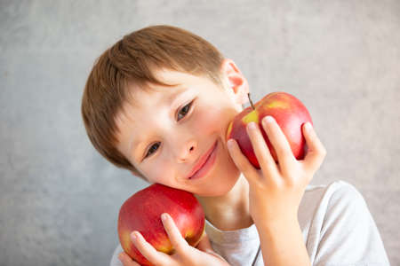 Child with fruit. Funny boy holds red big apples Stock Photo