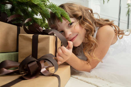 Funny child at christmas. Girl under the Christmas tree with gifts.