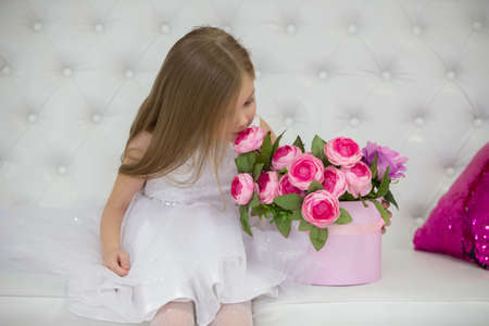 Beautiful child girl sniffing flowers.
