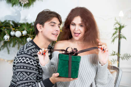 A man gives a woman a Christmas present. Husband and wife in the New Year holidays. Get a surprise in the winter holidays. Christmas holidays concept.