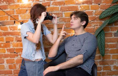 Girl photographer photographs a guy against a brick wall