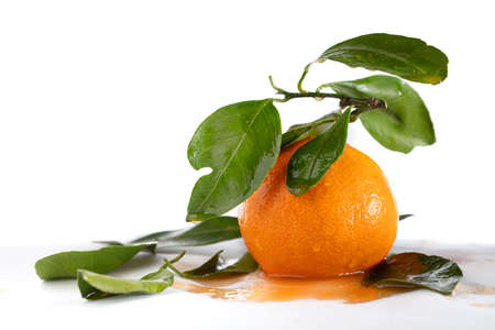 Mandarin with juice and leaves on a white background. Beautiful fruit.