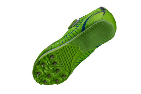 Green sole with spiked sneakers on a white background. Sport shoes.