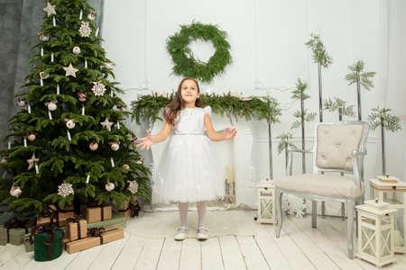 Elegant child at the Christmas tree. Little joyful girl in christmas