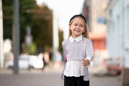 Joyful little girl on the street of the city. A child in an urban setting.
