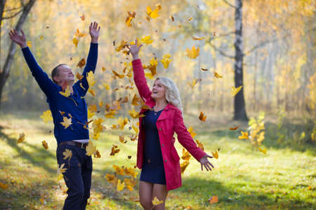 Loving couple in the autumn park. Spouses of middle age for a walk.Men and women throw yellow leaves