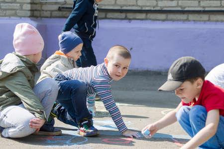 May 30, 2019 Belarus, Gomil. Kindergarten open day.Children from kindergarten draw with crayons on the asphalt. Sajtókép