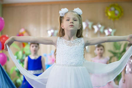 May 30, 2019 Belarus, Gomil. Kindergarten open day.Beautiful preschool girl in a white dress at the matinee.