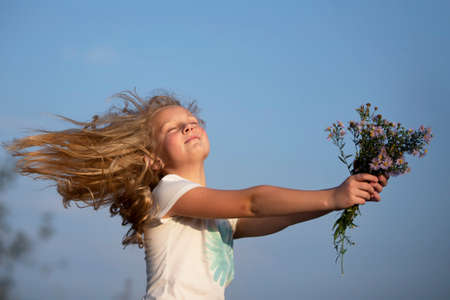Beautiful little girl with a bouquet of wild flowers on a background of the sky. A happy child on a summer meadow. Banco de Imagens