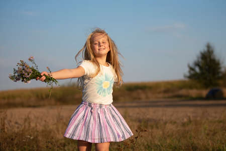 Beautiful little girl with a bouquet of wild flowers on a background of the sky. A happy child on a summer meadow. Stock fotó