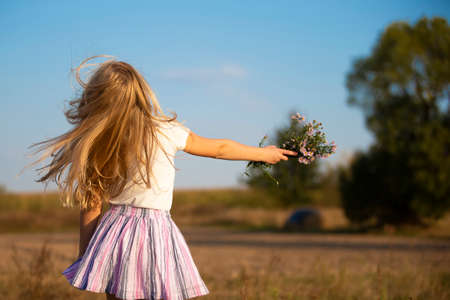 Happy little girl runs on the meadow with a bouquet of flowers. Child on a beautiful summer field against the blue sky.