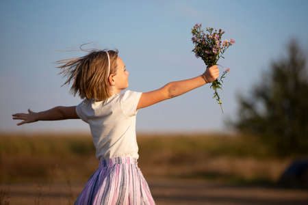 Beautiful little girl in the meadow with a bouquet of flowers. A child in a beautiful summer field. Banco de Imagens