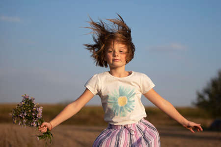 A beautiful joyful little girl in a meadow with a bouquet of flowers is jumping. A child in a beautiful summer field.