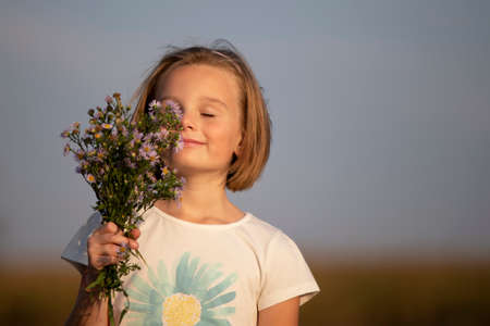 Beautiful little girl with a bouquet of meadow flowers. A child in a beautiful summer field.