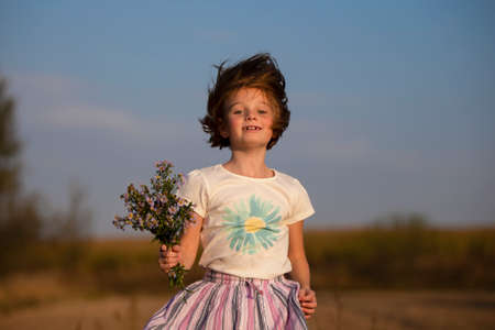 Happy little girl in the meadow with a bouquet of flowers. A child on a beautiful summer field with developing hair.