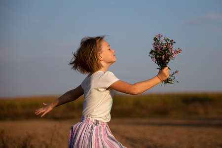 Beautiful little girl in the meadow with a bouquet of flowers. A child in a beautiful summer field. Stock fotó