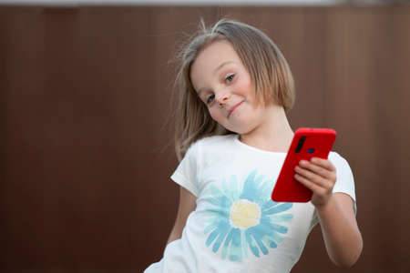 Child with a smartphone. Funny little girl dancing with a red phone. Stock fotó