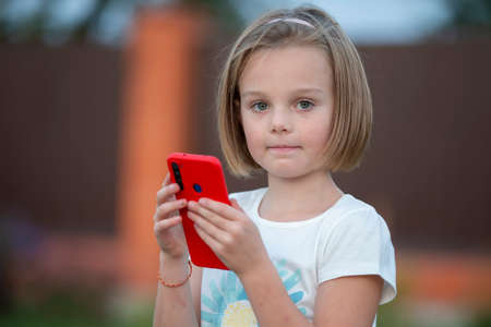 Child with a smartphone. Funny little girl with a red phone. Stock fotó