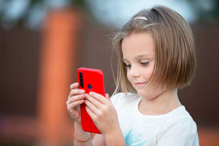 Child with a smartphone. The little girl is talking with a red phone.
