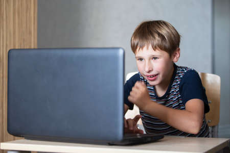 Schoolboy during online lesson at home, social distance during quarantine, self-isolation, online education concept. Elementary age boy at laptop at home.