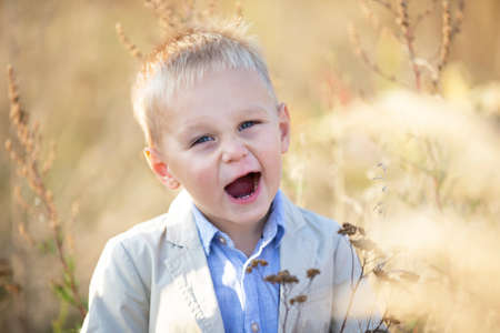 Funny cheerful little boy with blond hair smiles and looks into the camera. Stock fotó