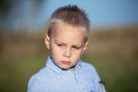 Sad little boy with blond hair in a blue shirt.