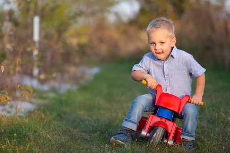 A little boy on a red motorcycle rides on the green grass.