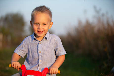 Cheerful little boy is holding a red rudder of a toy motorcycle and smiling for the camera. Stock fotó