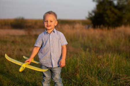 Little boy in the field plays with an airplane. Stock fotó
