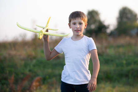 Little boy in the field plays with a yellow plane.