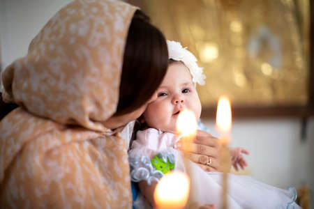 Belarus, Gamel, 15.07.2020. Church of Volotovo. Baptism of the Child.The newborn with his mother in the church among the candles