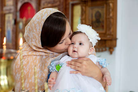 Belarus, Gamel, 15.07.2020. Church of Volotovo. Baptism of the Child.Mom kisses the child in the church. Sajtókép