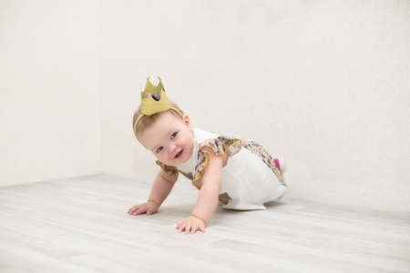 A one-year-old girl with a crown. The little princess crawls on the floor