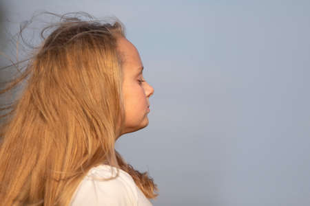 Little blonde girl in profile close-up on a background of blue sky. Imagens
