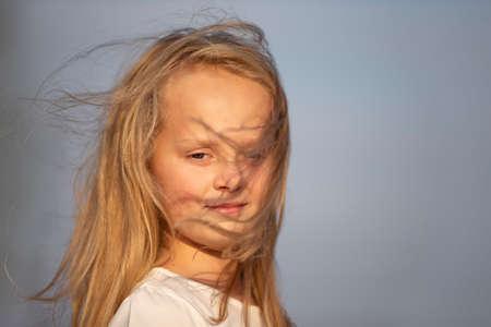 Little blonde girl with long hair against the sky. Stock fotó