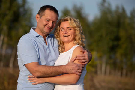 A beautiful middle-aged couple in love are hugging and looking at the camera.